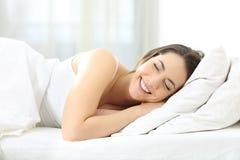 Sommeil heureux de femme confortable dans un lit photo stock