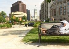 Sommeil sans abri d'homme sur un banc au centre de Philadelphie photo libre de droits