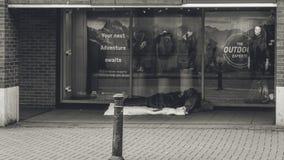 Sommeil sans abri en dehors du magasin photo stock