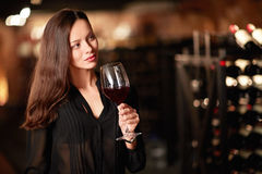 Sommelier. Young girl with a glass of wine in the cellar Stock Photo