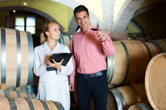 Sommelier advising male customer in winery cellar Stock Photos