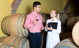Sommelier advising male customer in winery cellar Royalty Free Stock Images