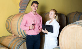 Sommelier advising male customer in winery cellar Royalty Free Stock Image