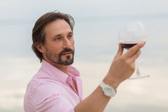 Sommelier. Analyzing a glass of red wine isolated on blue sky background. Black-haired mature man happy looking at the glass Stock Image