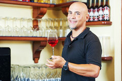Sommelier barman with glass of water. Portrait of sommelier barman holding a glass of water with wine glasses in the bar background Stock Image