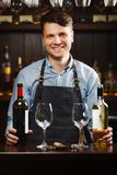 Sommelier with bottles of red and white wine and wineglasses. Sommelier with two bottles of red and white wine and wineglasses stands behind the bar. Smiling Royalty Free Stock Image