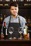 Sommelier with bottles of red and white wine and wineglasses. Sommelier with two bottles of red and white wine and wineglasses stands behind the bar. Bartender Royalty Free Stock Images