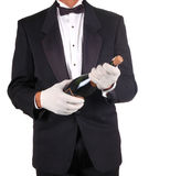Sommelier With Champagne. Sommelier in Tuxedo With Champagne Bottle isolated over white Royalty Free Stock Photography