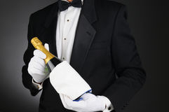 Sommelier with Champagne Bottle. Closeup of a Sommelier holding a Champagne bottle in front of his torso. Man is unrecognizable. Horizontal format on a light to Royalty Free Stock Photography