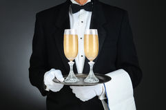 Sommelier with Champagne Glasses on Tray. Closeup of a Sommelier holding two champagne glasses on a tray in front of his torso. Horizontal format on a light to Royalty Free Stock Photography