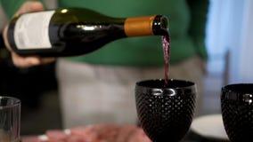 Sommelier che assaggia il vino nella cantina, sta versando un vino rosso eccellente in un vetro stock footage