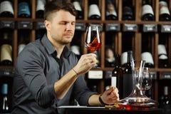 Sommelier che esamina il vetro del vino rosso con la bevanda fotografia stock
