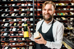 Sommelier with cheese and wine. Portrait of a sommelier in uniform with blue cheese and bottle of wine at the restaurant or supermarket. Choosing wine according stock photos