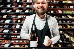 Sommelier with cheese and wine. Portrait of a sommelier in uniform with brie cheese and bottle of wine at the restaurant or supermarket. Choosing wine according royalty free stock image
