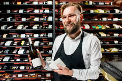 Sommelier with cheese and wine. Portrait of a sommelier in uniform with brie cheese and bottle of wine at the restaurant or supermarket. Choosing wine according royalty free stock photos