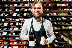 Sommelier with cheese and wine. Portrait of a sommelier in uniform with brie cheese and bottle of wine at the restaurant or supermarket. Choosing wine according royalty free stock photo