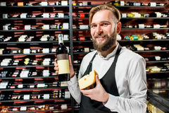 Sommelier with cheese and wine. Portrait of a sommelier in uniform with gouda cheese and bottle of wine at the restaurant or supermarket. Choosing wine according stock images