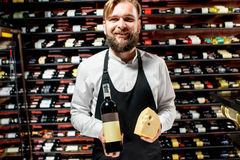 Sommelier with cheese and wine. Portrait of a sommelier in uniform with gouda cheese and bottle of wine at the restaurant or supermarket. Choosing wine according stock photography