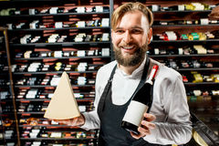 Sommelier with cheese and wine. Portrait of a sommelier in uniform with parmegiano cheese and bottle of wine at the restaurant or supermarket. Choosing wine royalty free stock photography
