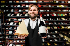 Sommelier with cheese and wine. Portrait of a sommelier in uniform with parmegiano cheese and bottle of wine at the restaurant or supermarket. Choosing wine royalty free stock photo