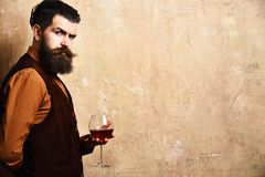 Sommelier with confident face drinks wine glass. Man with beard and mustache holds wine on beige wall background, copy space. Service and profession concept stock photos