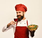 Sommelier and cooking service concept. Cook with smile. In burgundy uniform holds baked dish and wine. Chef holds bowl with potato casserole and glass of red stock image