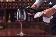 Sommelier cosechado de la visión que vierte el vino rojo de la botella en el vidrio en la tabla fotos de archivo