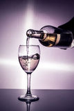 Sommelier fills a glass of wine. A bottle and a glass of wine in the backlight royalty free stock images