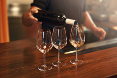 Sommelier fills the glasses during pinot gris wine tasting. Sommelier pours pinot gris wine in glasses for degustation royalty free stock photo