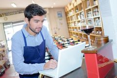 Sommelier in front laptop at wine cellar. Sommelier in front of laptop at wine cellar Stock Photos
