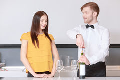 Sommelier and girl on a kitchen. Wine degustation. Handsome sommelier with bow tie helping young attractive women to choose wine at the degustation Royalty Free Stock Photo