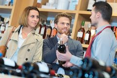Sommelier helping couple in shop. Sommelier helping a couple in a shop Royalty Free Stock Image