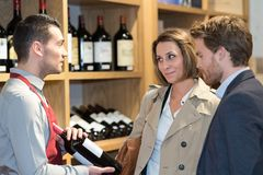 Sommelier helping couple to choose bottle wine Stock Photos