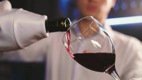 Sommelier in het restaurant giet rode wijn in een glas stock videobeelden
