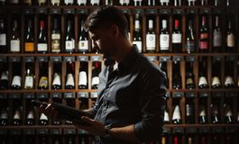 Sommelier holding big wine bottle in hands dark. Sommelier holding big wine bottle in hands and looking attentively on it, dark photo in cellar having collection stock photos