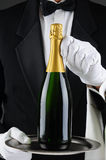 Sommelier Holding Champagne Bottle on Tray. Closeup of a sommelier holding a champagne bottle on a serving tray in front of his torso. Man is wearing a tuxedo Stock Photography
