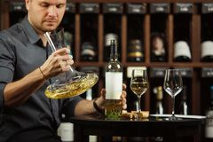 Sommelier holding decanter in hands full of wine. Sommelier holding decanter in hand filled with white wine in order to mix alcohol beverage and define natural stock images