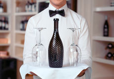 Sommelier holding tray with wine bottle. Everything is ready. Close up of tray with wine bottle in professional waiter holding it while being involved in work Stock Image