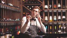 Sommelier joven elegante que habla en el teléfono con el comprador almacen de metraje de vídeo