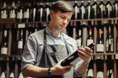 Sommelier joven que sostiene la botella de vino rojo en sótano imagen de archivo