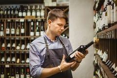 Sommelier joven que sostiene la botella de vino rojo en sótano foto de archivo libre de regalías