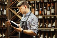 Sommelier joven que sostiene la botella de vino rojo en sótano imagen de archivo libre de regalías