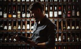 Sommelier jugeant la grande bouteille de vin dans des mains foncée photos stock