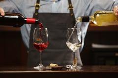 Sommelier maschio che versa vino rosso e bianco nei bicchieri di vino dal gambo lungo Fotografia Stock Libera da Diritti