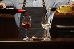 Sommelier maschio che versa vino rosso e bianco nei bicchieri di vino dal gambo lungo Fotografie Stock