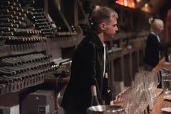 Sommelier maschio che versa vino rosso nei bicchieri di vino dal gambo lungo Fotografie Stock Libere da Diritti