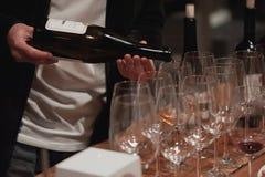Sommelier maschio che versa vino rosso nei bicchieri di vino dal gambo lungo Immagine Stock