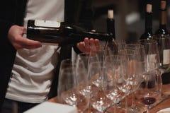 Sommelier maschio che versa vino rosso nei bicchieri di vino dal gambo lungo Fotografie Stock
