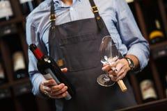 Sommelier masculin et juste bouteille ouverte avec le vin rouge Image libre de droits