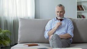 Sommelier masculin professionnel appréciant la saveur parfaite du vin rouge, passe-temps Image stock